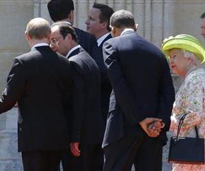 Vladimir Putin, left, talks to Francois Hollande, 2nd right, as they walk next to Barack Obama, center, and Queen Elizabeth, after posing for a group photo, June 6, 2014.