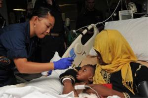 Hospital Corpsman 2nd Class Katherine Stafford treats a mother and child after a medical evacuation aboard the USS Bataan on June 7, 2014.