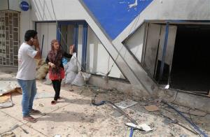 Iraqi civilians inspect the damages in the aftermath of a bomb in a commercial street in Baghdad, Iraq, Thursday, June 5, 2014.