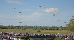 Paratroopers, watched by the crowd, are dropped from a US Air force Hercules C130, near Sainte Mere Eglise, western France, Sunday, June 8, 2014, as part of the 70th anniversary of D-Day.