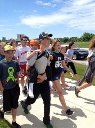 "Hunter Gandee, 14, walks in Saline, Mich., on Sunday, June 8, 2014, during the second day of his two-day, 40-mile ""Cerebral Palsy Swagger."