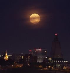 A full moon rises through clouds behind downtown buildings Sunday, June 23, 2013, in Kansas City, Mo.