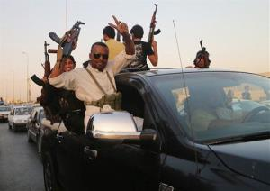 Shiite tribal fighters raise their weapons and chant slogans in Basra yesterday.