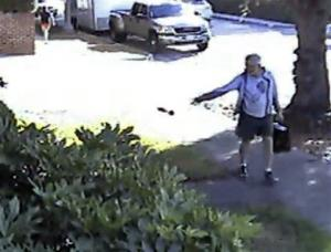 In this June 7, 2014 image from from a security video provided by Philip Lao, Dennis Kneier tosses a bag of dog waste onto the property of his neighbor, Philip Lao, in San Marino.
