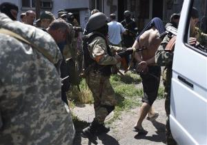 Ukrainian troops escort men detained at a battle site to a bus in Mariupol, eastern Ukraine, Friday, June 13, 2014.