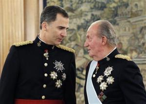 Spain's King Juan Carlos, right, talks to his son after handing over his military chief sash to him during a ceremony at the Zarzuela Palace in Madrid, Spain.