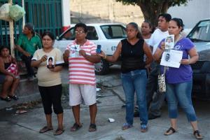 People hold portraits of their missing loved ones in front of the morgue of Cosamaloapan, after a mass grave was recently discovered, in Veracruz , Mexico, Wednesday, June 18, 2014.