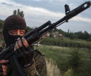 A pro-Russian fighter holds a gun during a handover of the bodies of Ukrainian troops killed in a plane shot down near Luhansk, at a check point in the village of Karlivka, June 18, 2014.