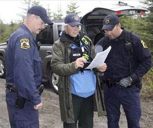 Kenai Police Sgts. Scott McBride, left, and Jay Sjogren review a map with Lisa Jaegar from the Mat-Su Search and Rescue Dogs on Monday, June 9, 2014, in Kenai, Alaska.