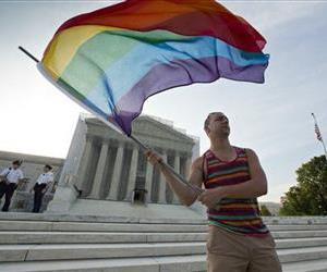 Gay rights advocate Vin Testa waves a rainbow flag in front of the Supreme Court at sun up in Washington, June 26, 2013.