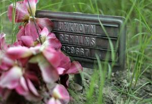 In this 2013 photo, a small sign at a cemetery marks the grave site of an unidentified body found on a ranch in Falfurrias, Texas.
