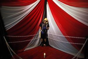 In this Friday, Jan. 31, 2014 photo, the body of boxer Christopher Rivera is propped up on a staged boxing ring during his wake in San Juan, Puerto Rico. Rivera was memorialized at his wake standing up in the makeshift boxing ring set up at a community center. Police said...
