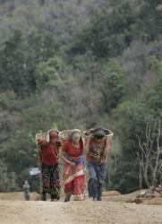 Local women carry items on their backs as they climb up a hill in Rolpa, Nepal, Wednesday, April 9, 2008.