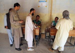 Afghan men line up to receive ballot papers for casting their votes at a polling station in Kabul, Afghanistan, Saturday, June 14, 2014.