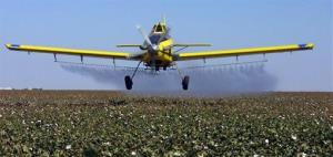 A crop dusting plane over a California field.