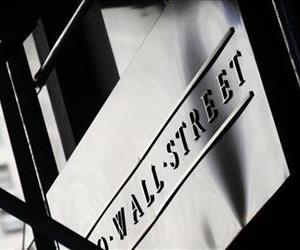A sign for Wall St. is shown outside the New York Stock Exchange, Monday, July 15, 2013 in New York.
