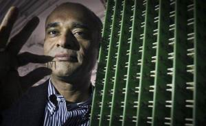 Chet Kanojia, founder and CEO of Aereo, Inc., stands next to a server array of antennas as he holds an antenna between his fingers.