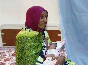 In this image provided June 5, 2014, by Al Fajer, a Sudanese NGO, Meriam Ibrahim breastfeeds her baby girl that she gave birth to in jail as the NGO visits her in a room at a prison in Khartoum, Sudan.