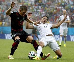 Germany's Bastian Schweinsteiger  is challenged by  Alejandro Bedoya of the US during their World Cup match at the Arena Pernambuco in Recife, Brazil, June 26, 2014.