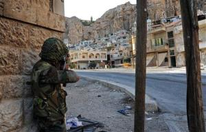 A Syrian government solider aims his weapon during clashes with anti-government rebels in this file photo.