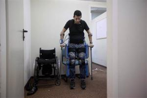 Radi Kaiuf, wounded and left paralyzed during his military service, gets up while strapped to a ReWalk device.
