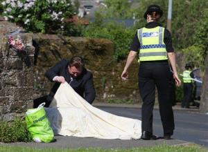 Police look under a sheet covering a body on Hagget End Road, in Egremont northwest England.