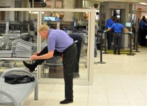 A traveler removes his shoes at Hartsfield-Jackson Atlanta International Airport on Wednesday, Jan. 15, 2014 in Atlanta.
