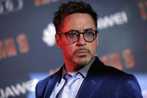 Robert Downey Jr. poses for photographers during the Iron Man 3 premiere, in Paris, Sunday April 14, 2013.
