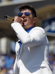 Musician Robin Thicke performs on the field prior to a baseball game between the San Francisco Giants and Los Angeles Dodgers on Saturday, April 5, 2014, in Los Angeles.