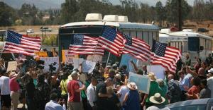 Protesters turn back three buses carrying 140 immigrants as they attempt to enter the Murrieta U.S. Border Patrol station for processing on Tuesday, July 1, 2014, in Murrieta, Calif.
