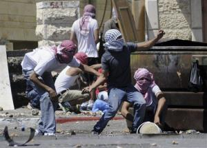 Palestinians throw stones during clashes with Israeli border police in Jerusalem on Wednesday, July 2, 2014.