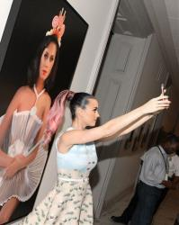 """Katy Perry takes a selfie with a painting of herself, """"Cupcake Katy"""" by artist Will Cotton, at the Smithsonian's National Portrait Gallery on Wednesday, June 25, 2014 in Washington."""