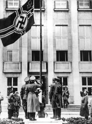 In this file photo taken in Sept. 1939, Nazi Germany, foreground left, and Soviet Red Army, foreground right, officers salute the Nazi swastika flag during their joint parade in Brest-Litovsk.