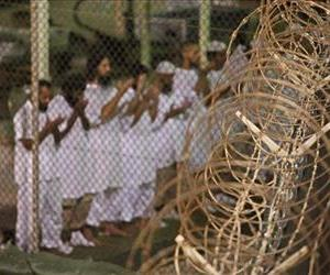In this May 14, 2009 file photo, reviewed by the US military, Guantanamo detainees pray before dawn near a fence of razor-wire, inside Camp 4 detention facility at Guantanamo Bay US Naval Base.