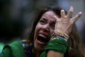 A Brazilian soccer fan cries as she watches her team get beat.