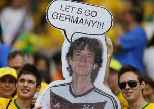 Brazil supporters hold a poster depicting Mick Jagger wearing a Germany shirt prior to the World Cup semifinal between Brazil and Germany in Belo Horizonte, Brazil, Tuesday, July 8, 2014.