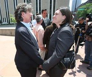 Two plaintiffs in a lawsuit to overturn Colordo's gay marriage ban, Cassie Rubald, left, and her partner, Rachel Catt, hold hands outside the federal courthouse in downtown Denver, July 1, 2014.