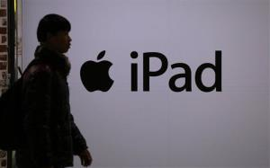 A man walks by a sign for Apple's iPad at shopping mall in Seoul, South Korea, Thursday, Dec. 12, 2013.