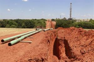 In this Friday, July 20, 2012 photo, pipe for a pipeline is readied for installation near a drilling rig, near Calumet, Okla.