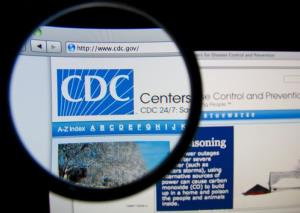 The United States Centers for Disease Control and Prevention homepage through a magnifying glass.