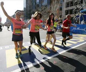 Celeste Corcoran, center, a victim of last year's bombings, reaches the finish line of the 118th Boston Marathon on April 21, 2014, with the aid of daughter Sydney, right, also wounded last year.