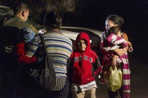 Mothers from Honduras traveling with their children prepare to get into a US Customs and Border Protection Services agent's truck after crossing the Rio Grande near McAllen, Texas.