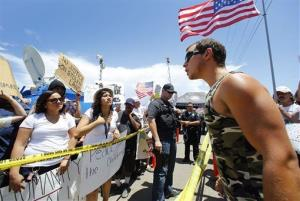 People from both sides of the issue argue across police lines during an immigration demonstration outside the Border Patrol  facility Friday, July 4, 2014 in Murrieta, Calif.
