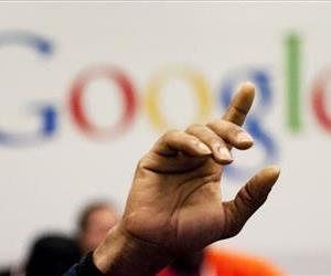 In this Oct. 17, 2012, file photo, a man raises his hand at Google offices in New York.