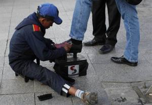 Lucas, 13, polishes shoes on a street in La Paz, Bolivia.
