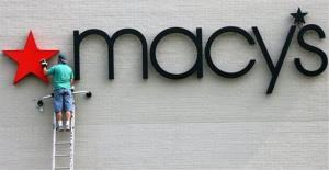 An unidentified sign company worker hangs the star in the Macy's department store logo on the outside of the Macy's in the Aurora Mall in Aurora, Colo., in this Sept. 7, 2006 file photo.