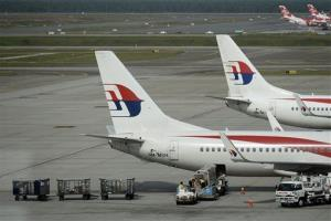 Malaysian Airlines ground crew loads cargo into a Malaysia Airline plane on the tarmac at Kuala Lumpur International Airport in Sepang, Malaysia, Saturday, July 19, 2014.