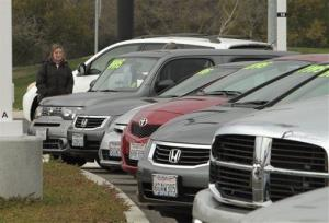 In this Jan. 11, 2011 file photo, a potential car buyer looks over used cars at a dealership in Sacramento, Calif.