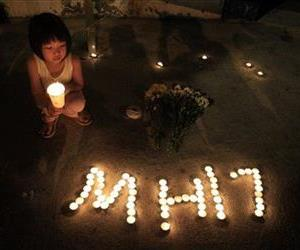 A girl holding a candle squats next to candles forming the letters MH17 during an event to mourn the victims of the crashed Malaysia Airlines Flight 17, in Kuala Lumpur, Malaysia, July 20, 2014.