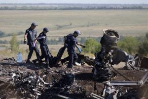 Ukrainian emergency workers carry a victim's body in a plastic bag at the crash site of Malaysia Airlines Flight 17 near the village of Hrabove in eastern Ukraine, July 21, 2014.